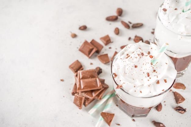 Warme chocolademelkshake, koude boozy cocktail met ijs of slagroom, met chocoladeschijfjes