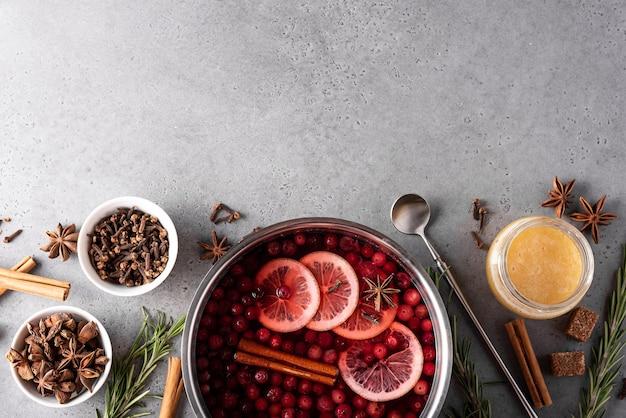 Warme cranberrydrank met citroenhoning en kruiden in een grijze pan, bovenaanzicht