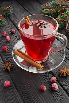 Warme cranberrydrank met kruiden in de glazen beker en kerstmissamenstelling op de zwarte houten achtergrond. locatie verticaal.