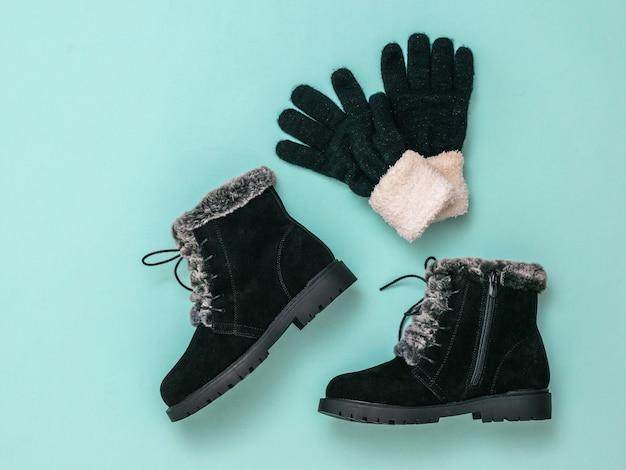 Warme dameslaarzen en gebreide handschoenen op een blauwe achtergrond. mode stijlvolle dames winterlaarzen. plat leggen.