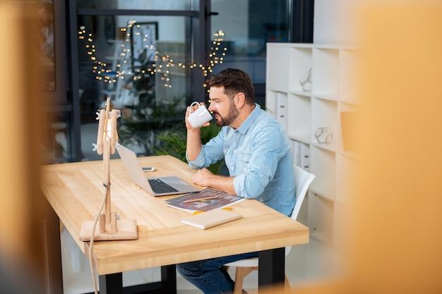 Warme drank. aangename aardige intelligente man die een kopje vasthoudt en een slokje thee drinkt terwijl hij op de laptop werkt