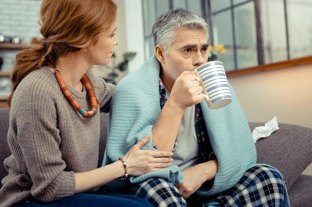 Warme drank. aardige zieke man die hete thee drinkt terwijl hij naast zijn vrouw op de bank zit