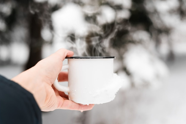 Warme drank bij koud weer. hand met stalen mok met warme drank buitenshuis, close-up. stoom stijgt op uit de mok