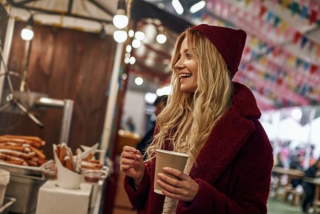 Warme drank in de herfst. zijaanzicht van een vrolijke vrouw die glühwein drinkt op de straatmarkt. koud seizoen. close-up foto van lachende blonde vrouw