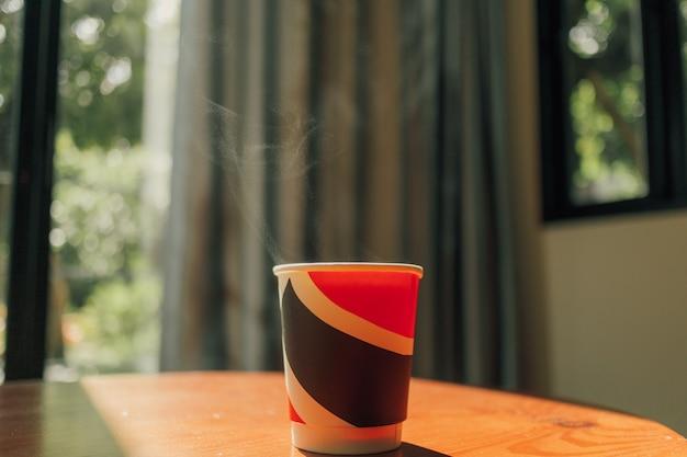 Warme drank in een kartonnen beker op tafel in warm ochtendlicht.