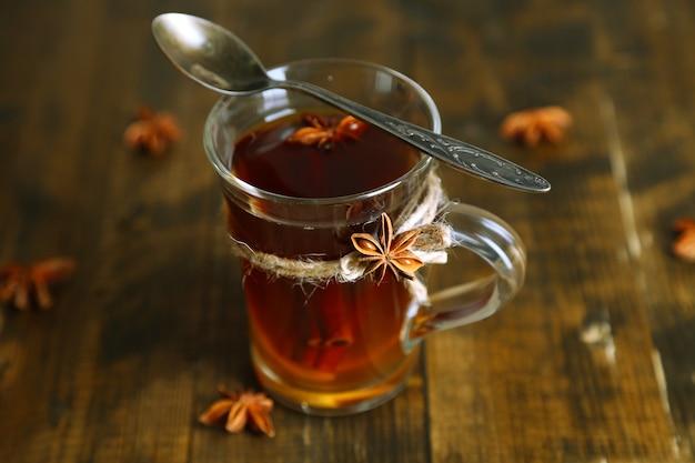 Warme drank in glazen beker met fruit en kruiden, op houten oppervlak
