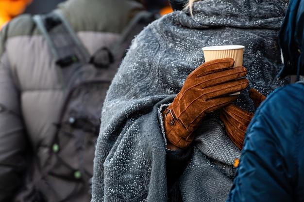 Warme drank in papieren bekers voor dranken met afhaalmaaltijden (thee of koffie) in handen met handschoenen, close-up