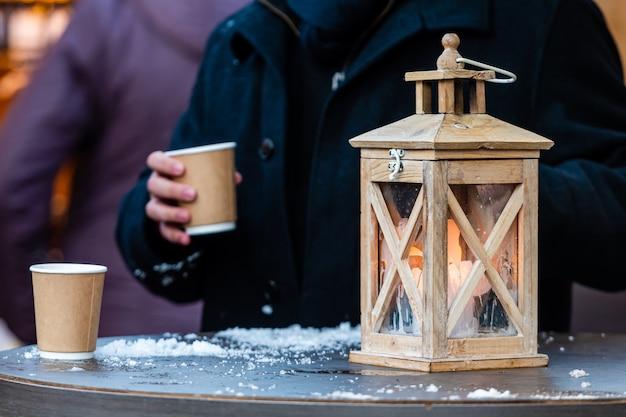 Warme drank in papieren bekers voor dranken met een afhaalmaaltijden (thee of koffie) in handen, lantaarn op de voorgrond, close-up