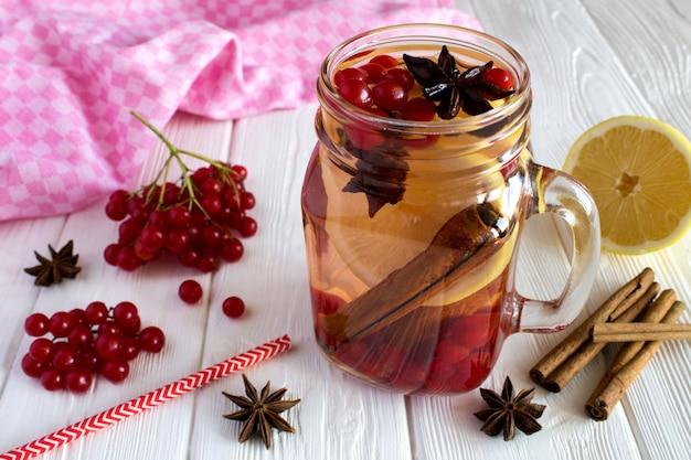 Warme drank met viburnum, citroen, kaneel en anijs op de witte houten achtergrond