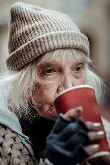 Warme drank. portret van een arme oude vrouw die een slokje thee neemt terwijl ze het drinkt