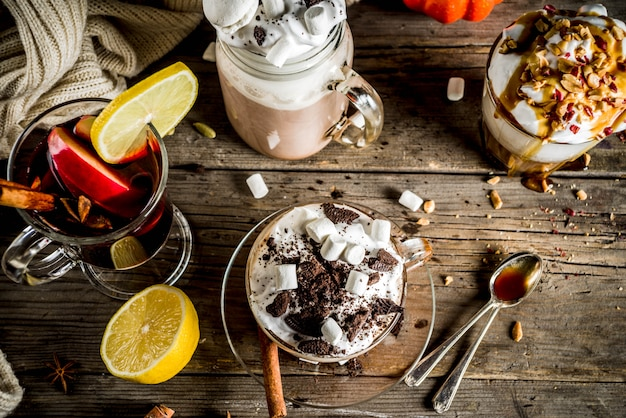 Warme dranken in de herfst, warme chocolademelk, pompoen latte, karamel en pindakoffie latte, glühwein, gezellige donkere achtergrond