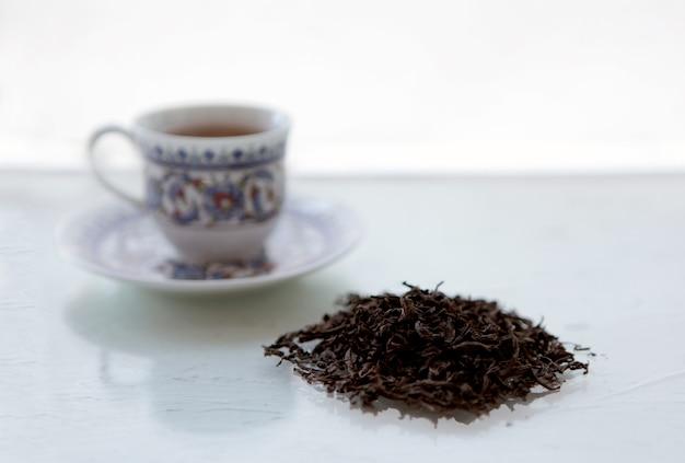 Warme drinkbeker. droge bladeren van zwarte chinese thee en theekopje op een witte achtergrond