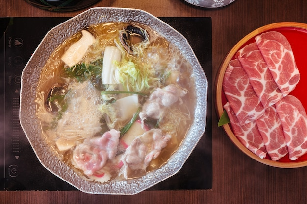 Warme en kokende shabu-bouillon met kool, eryngii, enotitake, tofu en kurobuta-varkensvlees in hete pot.