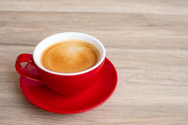 Warme espressokoffie op tafel, rode koffiekopje in café of thuis. bovenaanzicht met lege kopie ruimte voor uw tekst.