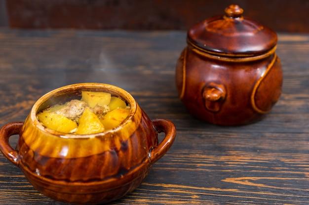 Warme gebakken aardappelen met kaas en kruiden in een aarden pot op een houten bureau. voedsel en dranken concept