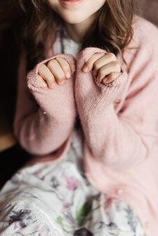 Warme gebreide jas. roze jasje op het meisje. gezellige huiskleding.