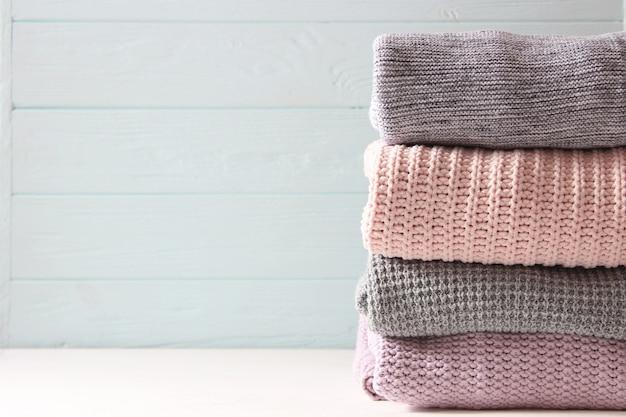 Warme gebreide truien gevouwen in een stapel op een lichte achtergrond close-up
