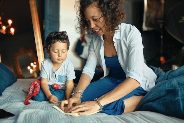 Warme, gezellige scène van een jonge spaanse vrouw zittend op bed met haar schattige zoon, papier vouwen, hem leren origami te maken.