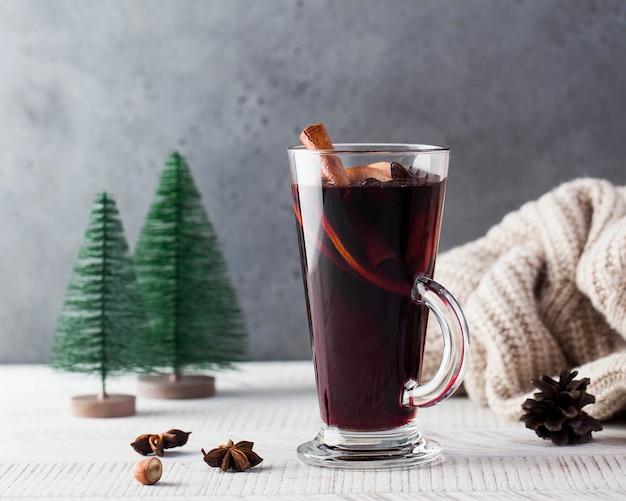 Warme glühwein in een glas met een kaneelstokje en kerstbomen