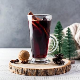 Warme glühwein in een glas met een kaneelstokje op een houten standaard en kerstbomen