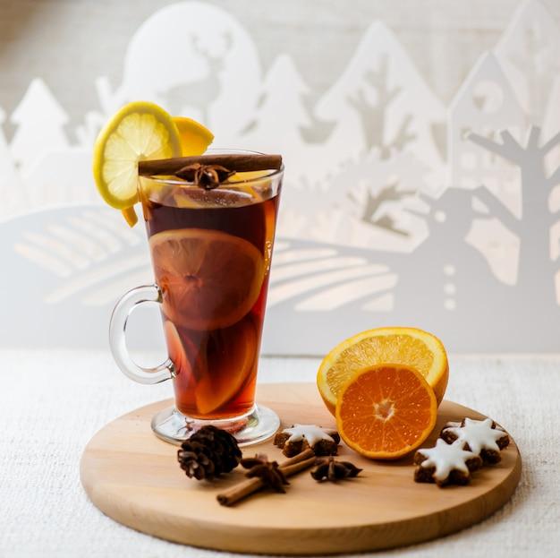 Warme glühwein in een glas met stukjes sinaasappel, anijs en kaneelstokjes, sterren cookies op vintage houten tafel.