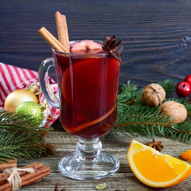 Warme glühwein in glazen mok op een houten tafel. geurige traditionele winterdrank op basis van wijn, sap, kruiden, smaakmakers, fruit.