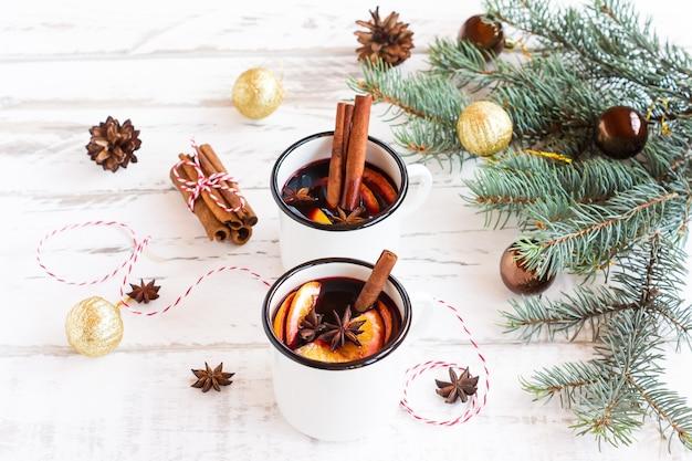 Warme glühwein op een houten ondergrond, met kruiden en sinaasappel- en dennenboomtakken met kerstballen.