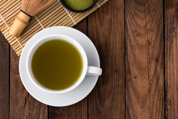 Warme groene thee in cup op hout