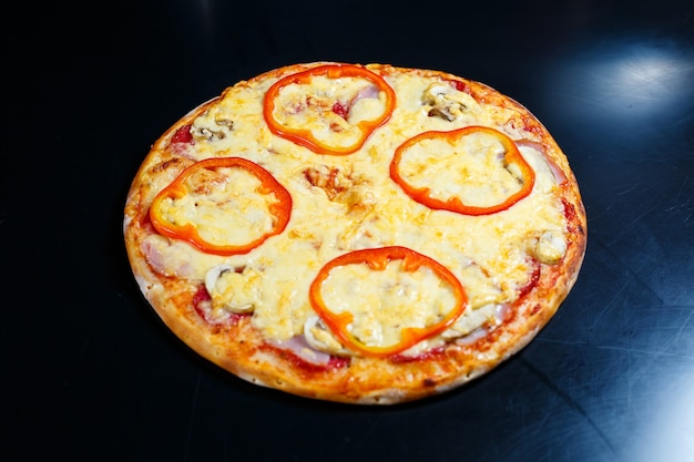 Warme heerlijke zelfgemaakte amerikaanse pizza met rode peper en vlees met een dikke korst op een zwarte tafel