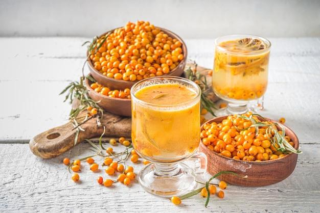 Warme herfst biologische drank. gezonde dieetdrank, immuniteitsbrekervoedsel. duindoornthee met sinaasappel en honing in glazen bekers. witte achtergrond kopie ruimte
