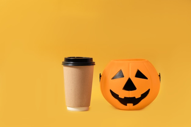 Warme herfstdrank om te gaan mock up cup halloween take away koffie pompoen geïsoleerde gele tekst of logo