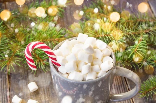 Warme koffie chocolademelk met marshmallow in kerststemming, feestelijke decoratie op rustieke houten tafel achtergrond, snoep stokken geschenkdozen rood lint fir tree versierd met sneeuw