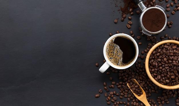 Warme koffie en bonen op zwarte houten tafel achtergrond. bovenaanzicht