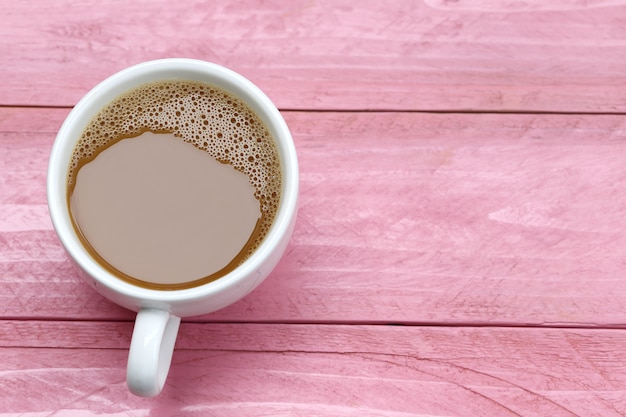 Warme koffie in een witte koffiekopje op roze houten tafel.