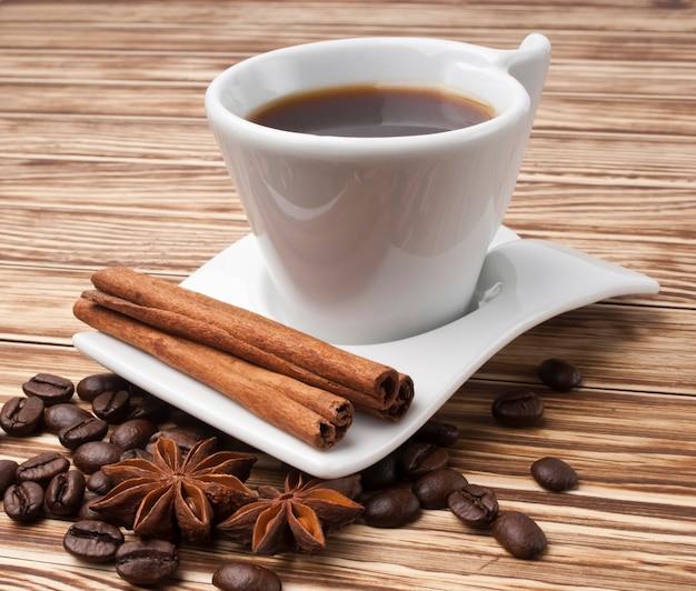 Warme koffie in witte kop op houten achtergrond
