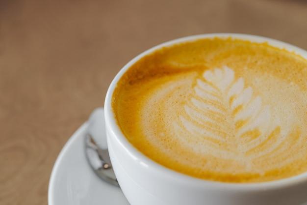 Warme koffie latte art op een witte kop op houten tafel achtergrond