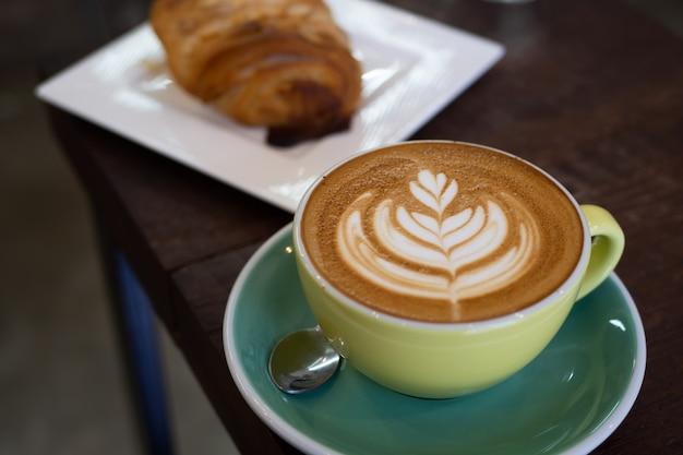 Warme koffie latte met prachtige schuimkunst op glazen tafel.