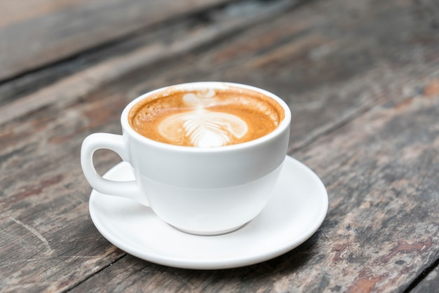 Warme koffie met late kunst op houten tafel