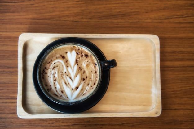 Warme koffie met latte art schuim op houten tafel in coffeeshop met kopieerruimte voor tekst door bovenaanzicht. drink en ontspan levensstijl.