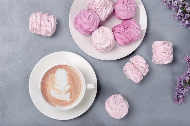 Warme koffie met roze marsmallow op grijze achtergrond