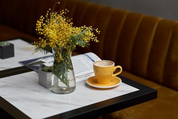Warme koffie vers dagboek, bloemmimosa bij het raam in het café
