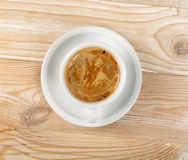 Warme koffiekopje op lichte houten tafel achtergrond bovenaanzicht met kopie ruimte.