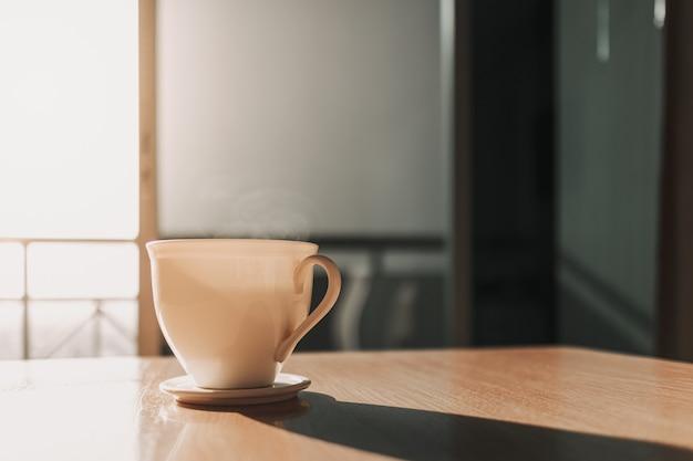 Warme kop drank op tafel in het zonlicht van een rustige ochtend
