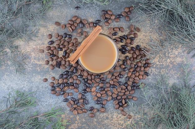 Warme kop koffie met kaneelstokje en koffiebonen op marmeren achtergrond. hoge kwaliteit foto