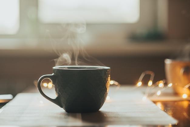 Warme kop thee of koffie. beker met stoom op tafel.
