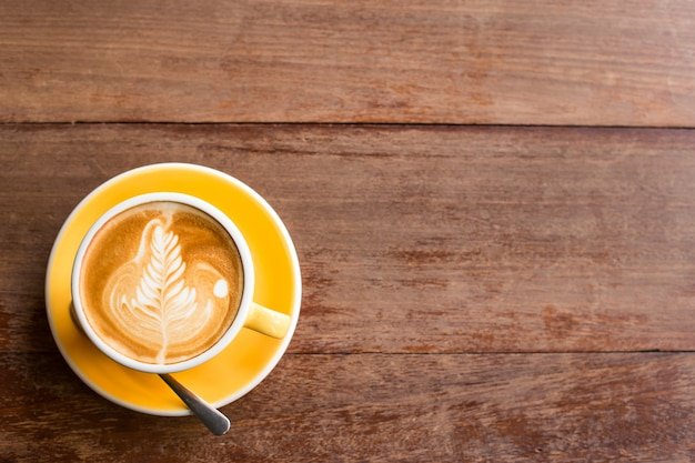 Warme kunst latte coffee in een kopje op houten tafel.