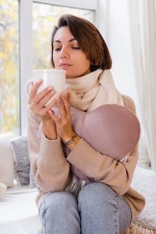 Warme portret van vrouw zittend op de vensterbank met kopje hete thee, koffie trui en witte sjaal dragen