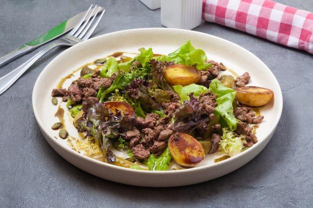 Warme salade met aardappelen, lever en ingelegde komkommer
