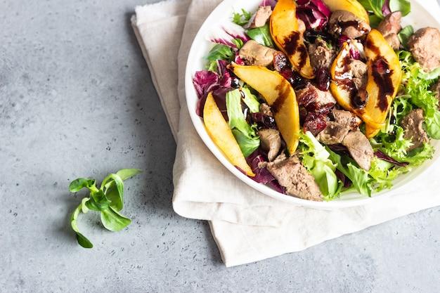 Warme salade met gebakken lever, gekarameliseerde peer, veenbessen en salademix.