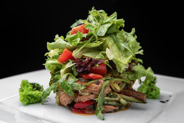 Warme salade met kalfsvlees, op een witte plaat, op een zwarte achtergrond. zijaanzicht